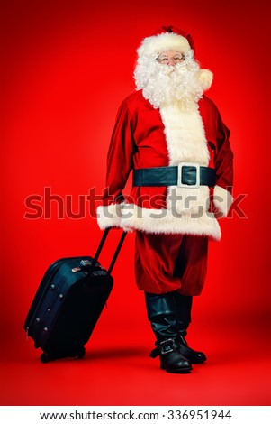 Santa Claus stands with modern suitcase over red background. Christmas time. Christmas tours. - stock photo