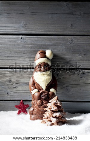Santa claus star shaped christmas decoration chocolate christmas tree on heap of snow against wooden background - stock photo