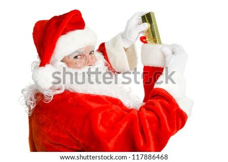 Santa Claus stuffing a christmas stocking.  Isolated on white. - stock photo