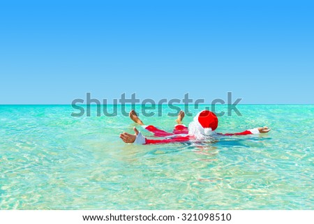Santa Claus take pleasure swimming  in ocean water, Christmas and New Year's vacation in hot countries concept - stock photo