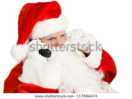 Santa Claus takes telephone call on his land line.  Isolated on white.