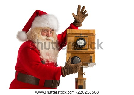 Santa Claus taking picture with old wooden camera - stock photo
