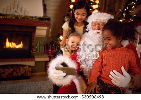 Santa Claus taking selfie during Christmas atmosphere at home with children