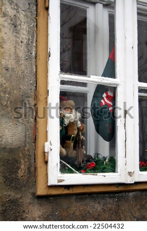 Santa Claus toy at old window (winter background)