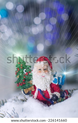 Santa Claus toy in snow on Christmas tree - stock photo