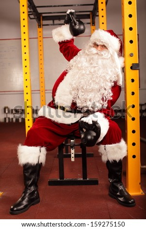Santa Claus training before Christmas  with kettlebells on bench in gym - - stock photo