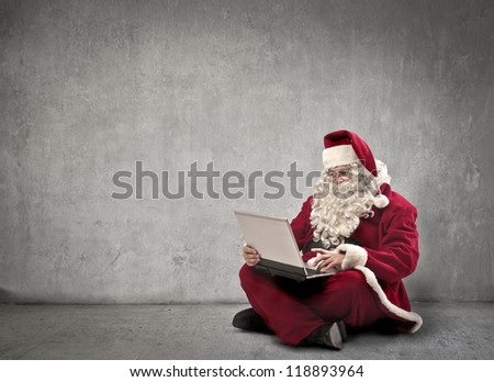 Santa Claus using a laptop computer in a white dark room - stock photo