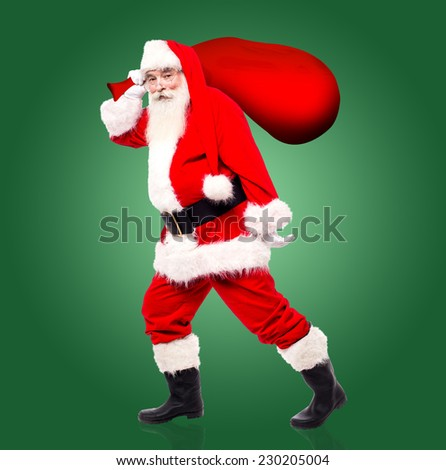 Santa claus walking away with gift bag to distribute the gifts - stock photo