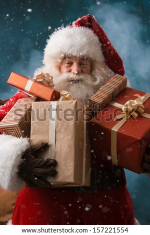 Santa Claus walking on the snow with his sack of lots of presents. Winter night with snowfall - stock photo