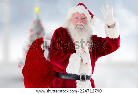 Santa claus waving against blurry christmas tree in room - stock photo