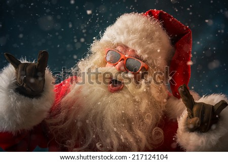 Santa Claus wearing sunglasses dancing outdoors at North Pole in snowfall. He is celebrating Christmas after hard work - stock photo