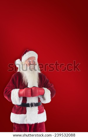 Santa Claus wears boxing gloves against red background - stock photo