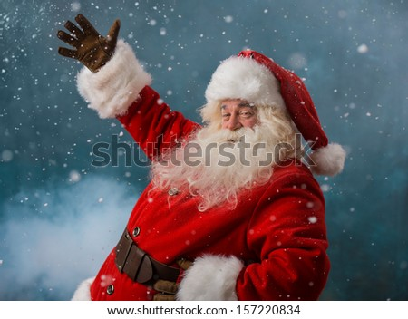 Santa Claus welcoming to the North Pole standing outdoors in snowfall - stock photo