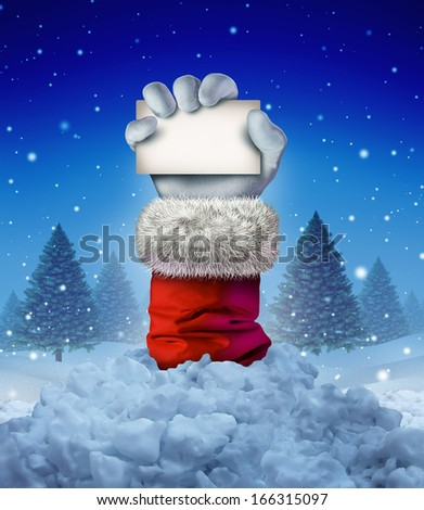 Santa Claus winter sign as a hand holding a blank card emerging out of a pile of avalanche snow in a pine forest scene as a funny Christmas symbol and joyous seasonal holiday celebration message.