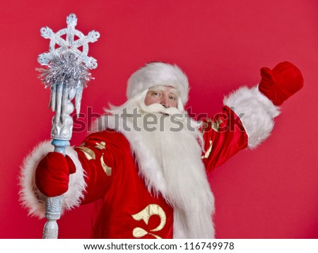 Santa Claus with a bag sitting welcomes on a red background