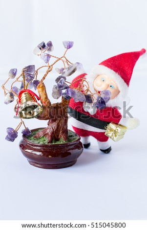 Santa Claus with a gift in hand and a Christmas tree with leaves of amethyst