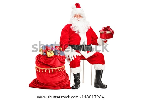 Santa Claus with a gift sitting next to a bag full of presents isolated on white background - stock photo