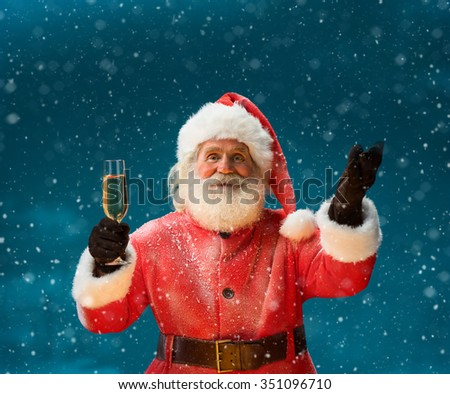 Santa Claus with a glass of champagne and looking at camera / Merry Christmas & New Year's Eve concept / Closeup on blurred blue background. - stock photo