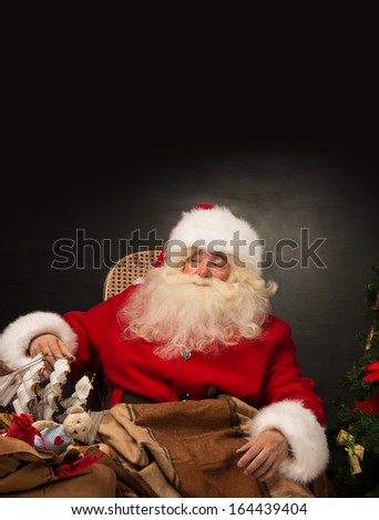 Santa Claus with a huge bag full of Christmas presents sitting in a comfortable chair near the Christmas tree at home. Lots of copyspace - stock photo