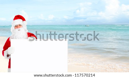 Santa claus with banner on the beach. - stock photo
