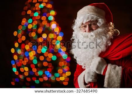 Santa Claus with big red sack looking at camera - stock photo