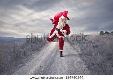 Santa Claus with big red sack runs in the country - stock photo