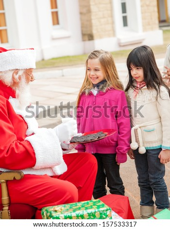 Santa Claus with biscuits and milk looking at children outside house