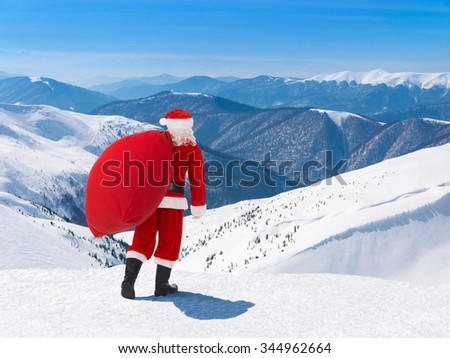 Santa Claus with Christmas bag full of presents against snowy winter mountain ski resort landscape and blue sky, New Year's or xmas greeting card - stock photo