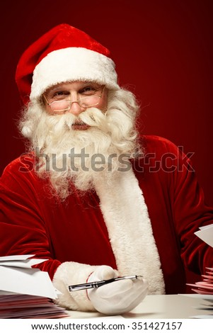 Santa Claus with Christmas letters looking at camera