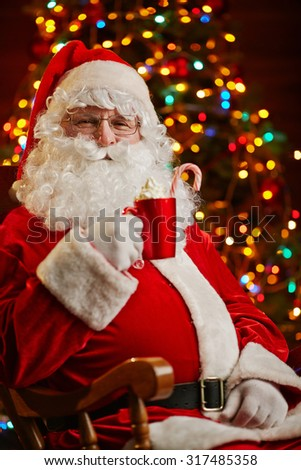 Santa Claus with cup of latte on background of Christmas tree