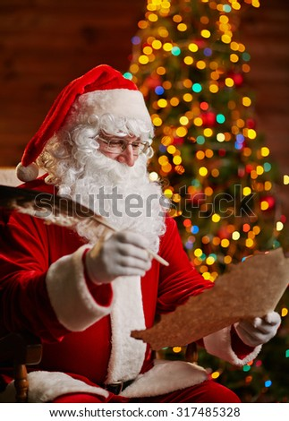 Santa Claus with feather answering Christmas letter - stock photo