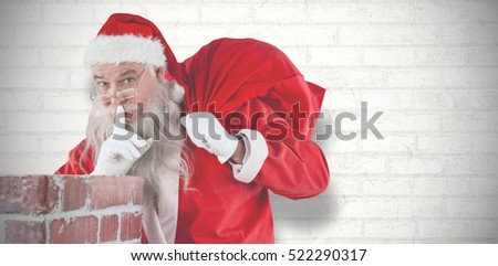 Santa Claus with finger on lips standing beside chimney against white wall