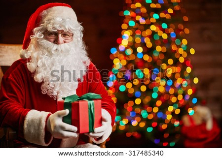 Santa Claus with giftbox on background of sparkling firtree