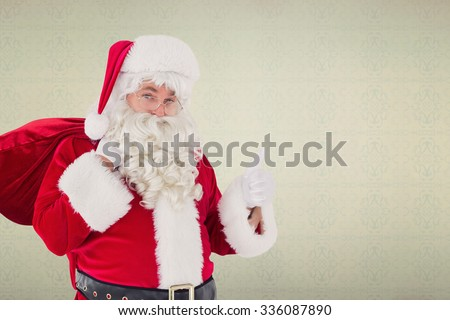 Santa claus with his sack and thumbs up against room with wooden floor - stock photo