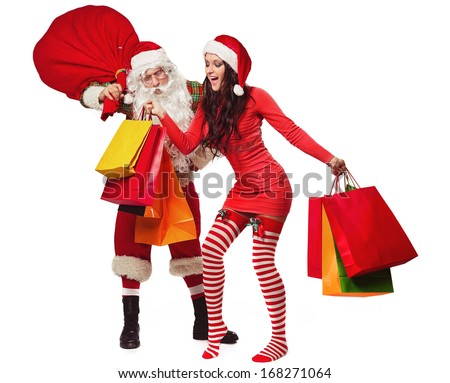 Santa Claus with his sack full of presents and smiling woman in red dress and santa helper hat with shopping bags - stock photo