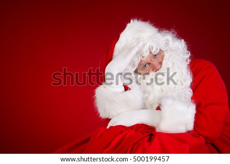 Santa Claus with huge bag full of christmas presents isolated on red background