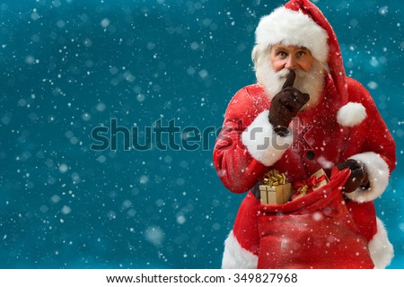 Santa Claus with huge red sack keeping forefinger by his mouth and looking at camera / Merry Christmas & New Year's Eve concept / Closeup on blurred blue background. - stock photo