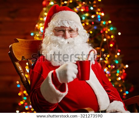 Santa Claus with latte in red cup sitting in armchair