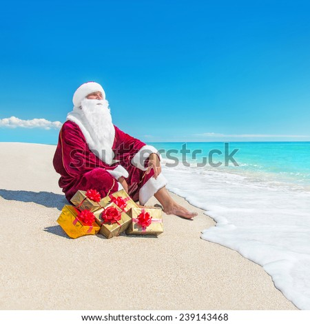 Santa Claus with many golden gifts at tropical beach  - christmas  or happy new year travel in hot countries concept - stock photo
