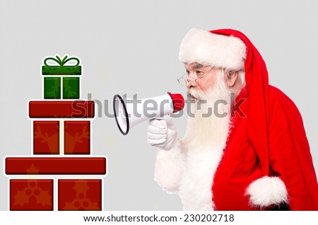 Santa Claus with megaphone and stack of gifts - stock photo