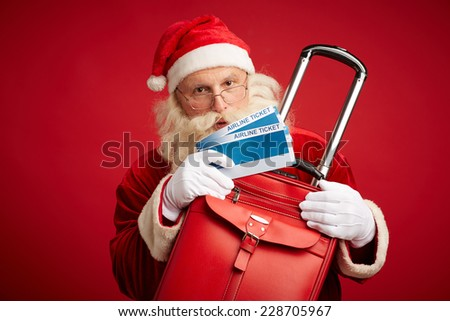 Santa Claus with red leather suitcase and airline tickets in isolation