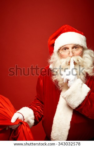 Santa Claus with sack of Christmas presents keeping forefinger by mouth