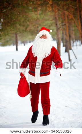 Santa Claus with sack walking down winter forest