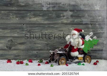 Santa Claus with vintage car, presents and tree on wooden snowy background.  Idea for a xmas greeting card. - stock photo