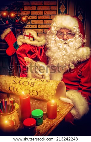 Santa Claus writing a list of good boys and girls at home. Christmas. - stock photo