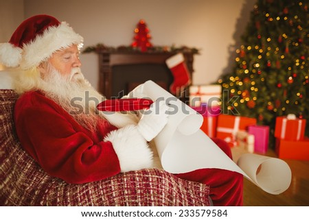 Santa claus writing his list on scroll at home in the living room