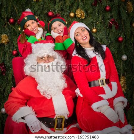 Santa Clause woman smiling elf helper sitting on Christmas armchair - stock photo