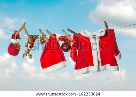 Santa clothes and christmas gifts hanging on a clothes line - stock photo