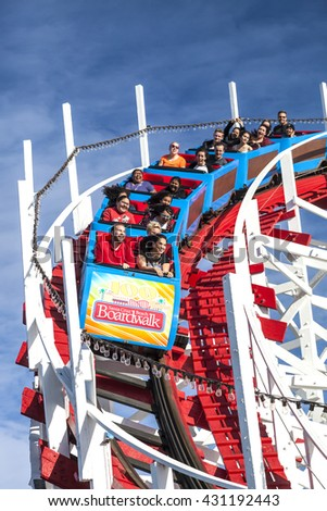 SANTA CRUZ, CALIFORNIA, USA-NOVEMBER 15, 2014 : People on Giant Dipper the fifth oldest wooden coaster in the US. Built by Arthur Looff in 1924 and maximum speed is up to 46 mph. Taken in Santa Cruz.