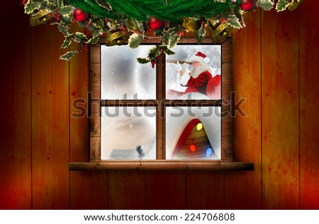 Santa delivery presents to village against festive christmas wreath - stock photo